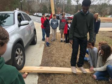 students lift car